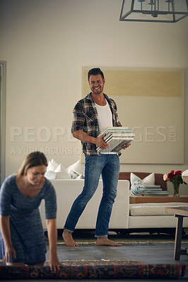 Buy stock photo Shot of a young beautiful woman rolling up a carpet while her handsome husband is carrying books at home