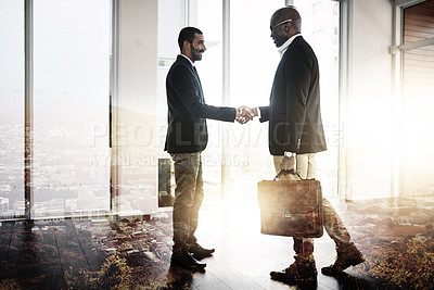 Buy stock photo Full length shot of two businessmen shaking hands in an office superimposed over a city background