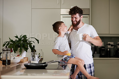 Buy stock photo Shot of an adorable little boy and his father having coffee and juice together at home