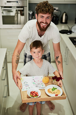 Buy stock photo Shot of an adorable little boy holding a tray of breakfast with his father for Mother's Day