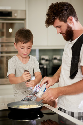 Buy stock photo Shot of an adorable little boy and his father making breakfast together at home