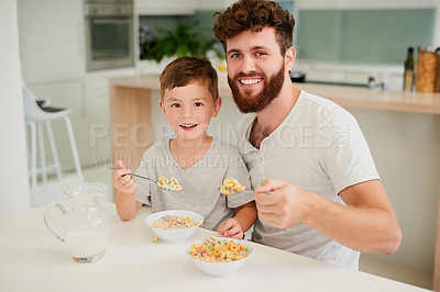 Buy stock photo Shot of an adorable little boy and his father having breakfast together at home