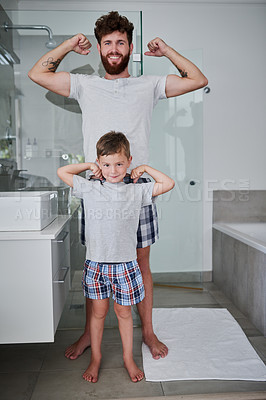 Buy stock photo Portrait of a father and his little son flexing their arms in the bathroom at home