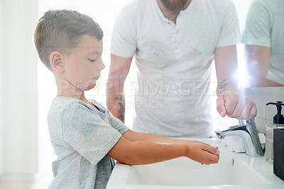 Buy stock photo Cropped shot of an unrecognizable father helping his adorable little boy wash his hands in the bathroom at home
