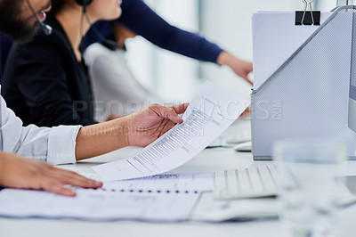 Buy stock photo Cropped shot of a man reading paperwork in a call center