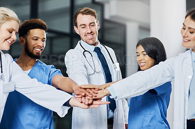 Buy stock photo Shot of a group of medical practitioners joining their hands together in a huddle