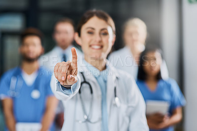 Buy stock photo Shot of a young doctor pointing in a hospital with her colleagues in the background