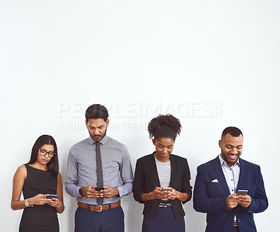 Buy stock photo Studio shot of a group of young businesspeople standing in line and using their mobile phones against a gray background