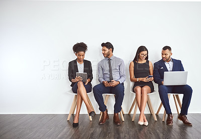 Buy stock photo Studio shot of a group of young businesspeople waiting in line against a gray background
