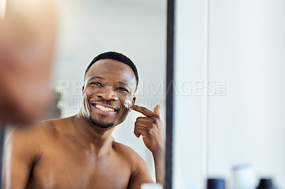 Buy stock photo Shot of a cheerful young male applying moisturizer to his face during his morning grooming routine