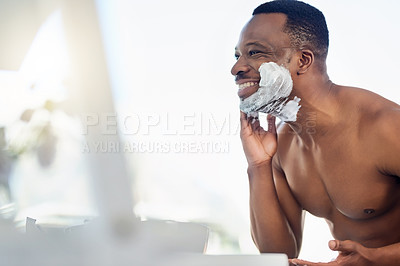 Buy stock photo Shot of a handsome young man shaving his facial hair in the bathroom