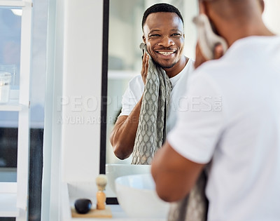 Buy stock photo Shot of a handsome young man examining his face in the bathroom mirror