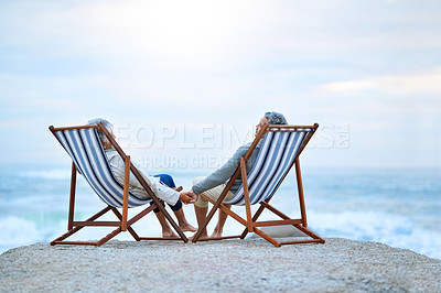 Buy stock photo Rearview shot of an affectionate senior couple sitting on loungers at the beach