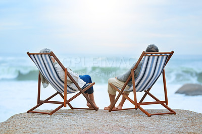 Buy stock photo Rearview shot of a senior couple sitting on loungers at the beach