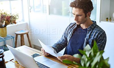 Buy stock photo Shot of a focused young man doing paperwork while being seated in front of his laptop at home