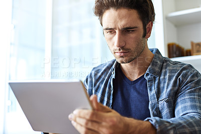 Buy stock photo Shot of a focused young man working on his digital tablet while being seated at home