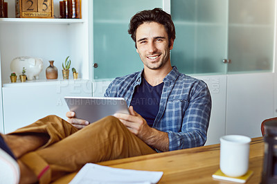 Buy stock photo Portrait of a cheerful young man working on a digital tablet while sitting with his feet up on a table at home