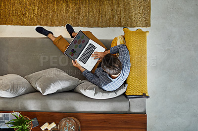 Buy stock photo High angle shot of a focused young unrecognizable man working on a laptop while relaxing on a couch at home