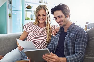 Buy stock photo Cropped shot of a young attractive couple planning their home budget together on the sofa in the living room at home