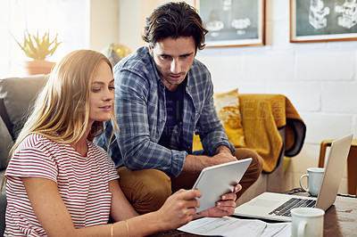 Buy stock photo Shot of a focused young couple working together on a digital tablet while being seated on a couch at home
