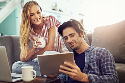 Buy stock photo Cropped shot of a young couple using wireless technology at home