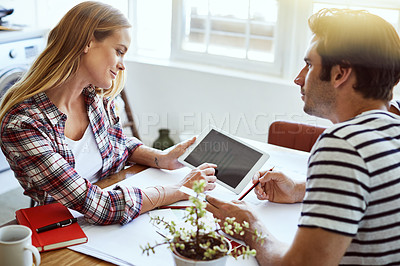 Buy stock photo Shot of a focused young couple drawing plans and choosing colors for the renovation of their house while making use of a digital tablet