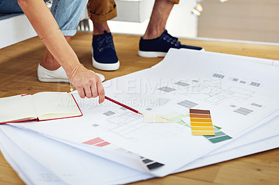 Buy stock photo Shot of an unrecognizable young couple drawing plans and choosing colors for the renovation of their house