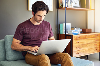 Buy stock photo Shot of a handsome young man using his laptop on the sofa at home