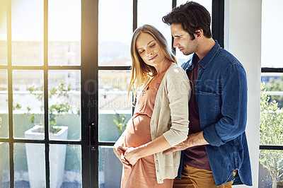 Buy stock photo Shot of a young man embracing his pregnant wife at home