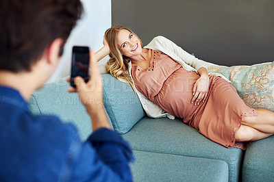 Buy stock photo Shot of a young man taking pictures of pregnant wife using a mobile phone on the sofa