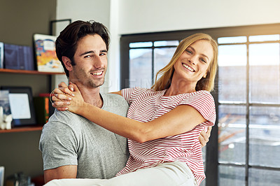 Buy stock photo Shot of a happy young man lovingly carrying his wife at home