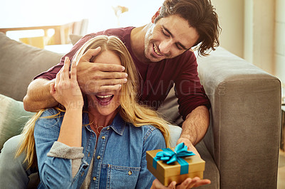 Buy stock photo Shot of a young man giving his wife a gift at home