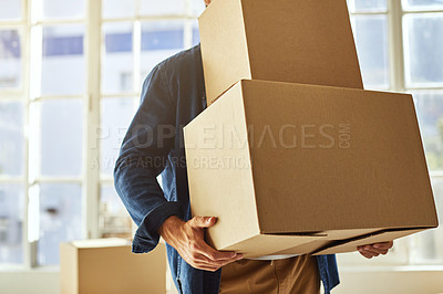 Buy stock photo Cropped shot of a young man carrying boxes while moving into his new home