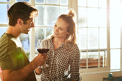 Buy stock photo Shot of a young couple toasting with wine at home