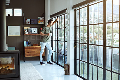 Buy stock photo Shot of a handsome young man having coffee while standing by a glass door at home