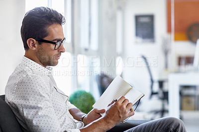 Buy stock photo Shot of a young businessman working in his office