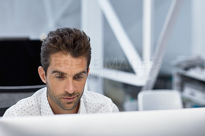 Buy stock photo Cropped shot of a young businessman working on his computer