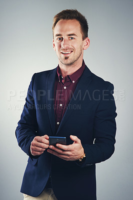 Buy stock photo Studio portrait of a confident young businessman using a mobile phone against a gray background
