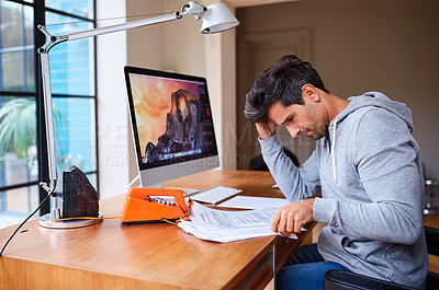 Buy stock photo Shot of a young man going through paperwork while working from home