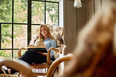 Buy stock photo Shot of a young woman reading a book while relaxing on a rocking chair at home