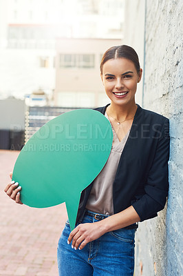 Buy stock photo Portrait of a young businesswoman holding a speech bubble outdoors
