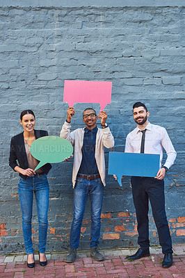 Buy stock photo Portrait of a group of businesspeople holding speech bubbles against a brick wall outdoors