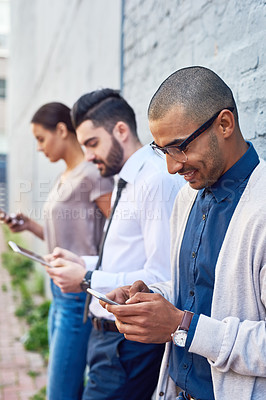 Buy stock photo Shot of a group of businesspeople using digital devices outdoors