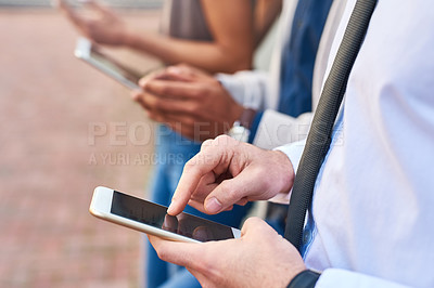 Buy stock photo Closeup shot of a group of unrecognizable businesspeople using digital devices outdoors
