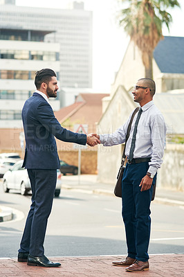 Buy stock photo Shot of two businessmen shaking hands while out in the city