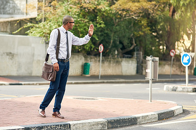Buy stock photo Shot of a young businessman gesturing to get a cab in the city