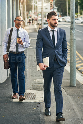 Buy stock photo Shot of two businessmen walking in the city