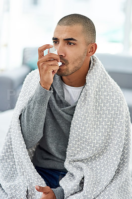 Buy stock photo Cropped shot of a young man using his asthma pump while feeling unwell at home