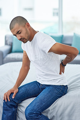 Buy stock photo Cropped shot of a young man holding his back in pain while sitting on the bed at home