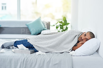 Buy stock photo Full length portrait of a young man lying on his bed while feeling unwell at home